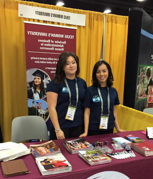 Two SHRM members at a conference with TWU banners behind them.