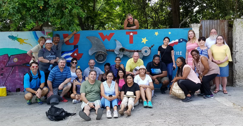 Dr. Rylander and Dr. Radighieri posing with students in front of a TWU painted wall in Cuba.