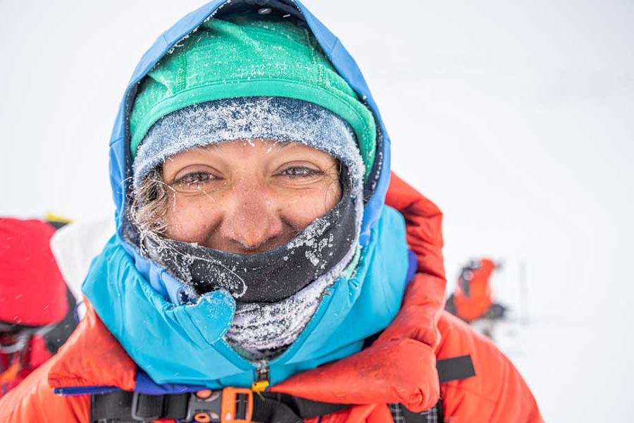 A selfie of Roxanne 冈萨雷斯 - 沃格尔 on a snowy mountain in Antarctica and wrapped in climbing and protective gear.