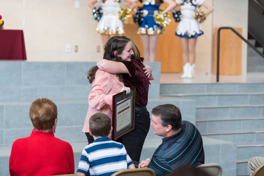 Caroline Deitch hugs her high school teacher in her high school auditorium.