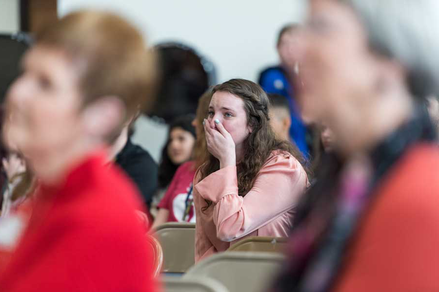 Caroline Deitch makes a surprised expression in a crowd in her high school auditorium.