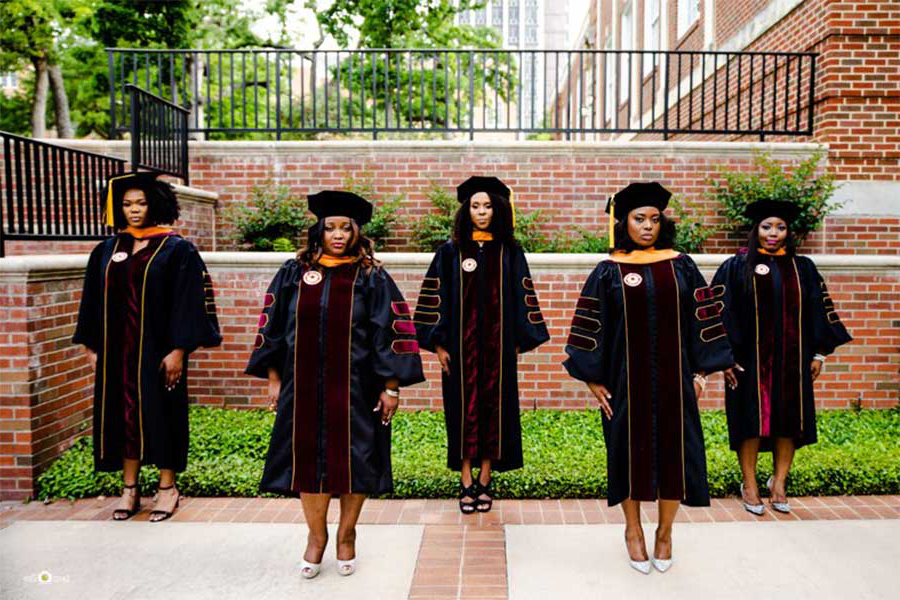 Five women in doctoral academic regalia pose outdoors.