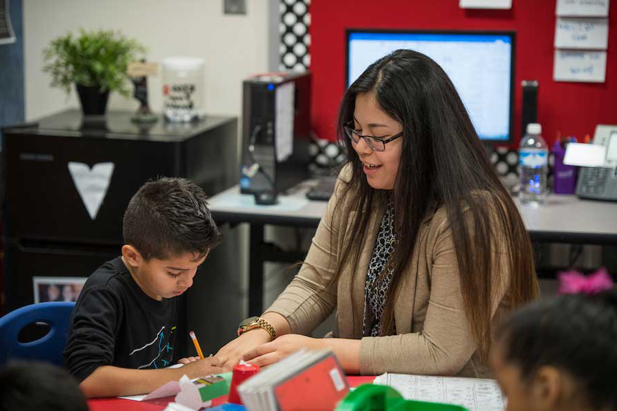 A hispanic TWU student teaches a young boy in a classroom setting.