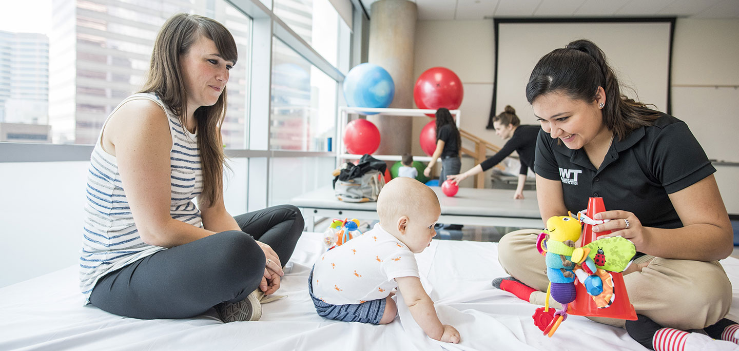 A TWU physical therapy student works with a small toddler