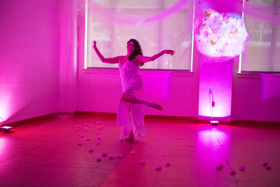 A dancer performs in a magenta room with a white globe