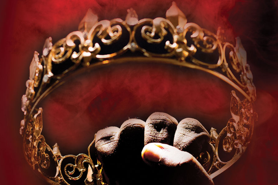Hand holding a crown in front of red, smokey backdrop